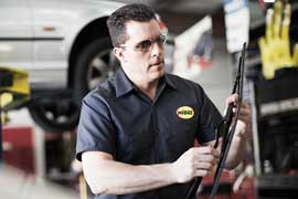 Midas mechanic changing windshield wipers